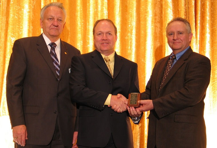 Luthi hands a corporate leadership award to an Exxon Mobil executive in 2008